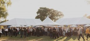 An image of large outdoor tents, people are mingling and holding glasses of wine