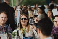 People surrounding a table with wine bottles smile at the camera
