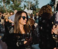A woman with a wineglass in a crowd
